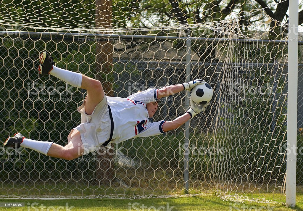 Goal keeper in mid air saving a ball stock photo