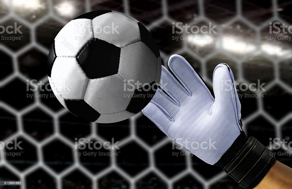 Goal keeper trying to catch a fast soccer ball stock photo