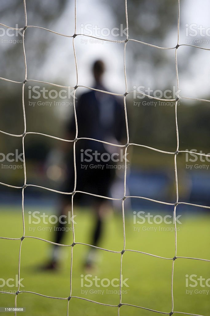 goal net and goalkeeper out of focus in the background royalty-free stock photo
