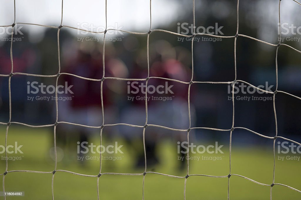 goal net with celebrating soccer players out of focus royalty-free stock photo
