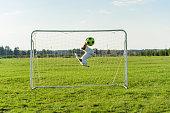 Goalie catching football ball saving goal