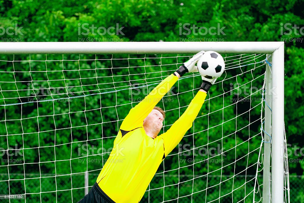 Goalie jumps and blocks soccer ball from scoring goal stock photo