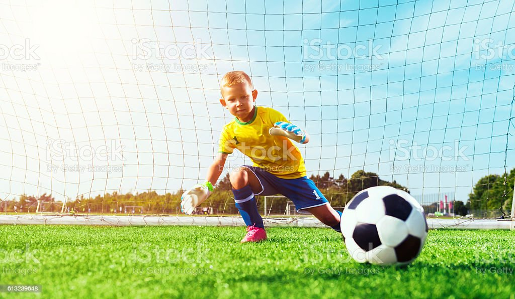 Goalie jumps and tries to block soccer ball stock photo
