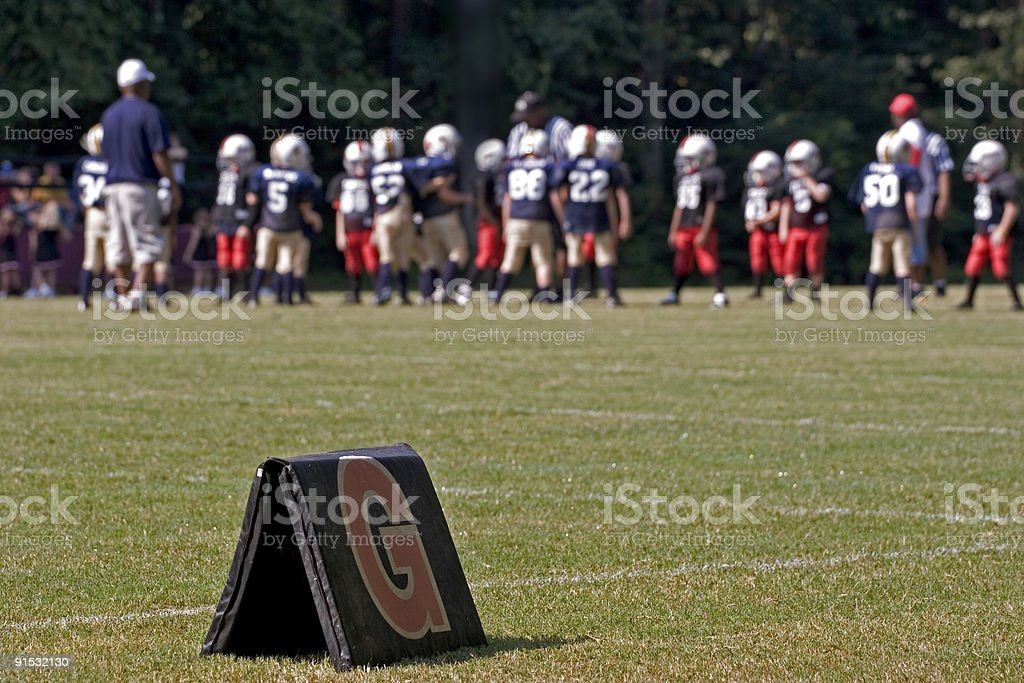 Goaline marker with peewee football teams in distance stock photo