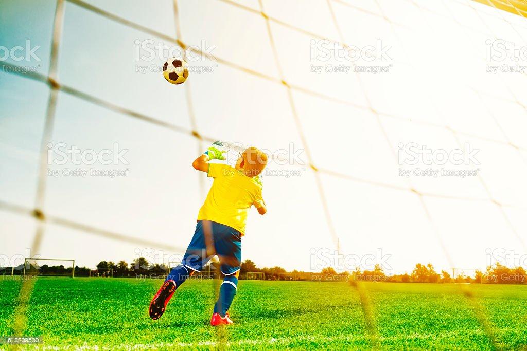 Goalkeeper boy blocks soccer ball from scoring goal stock photo