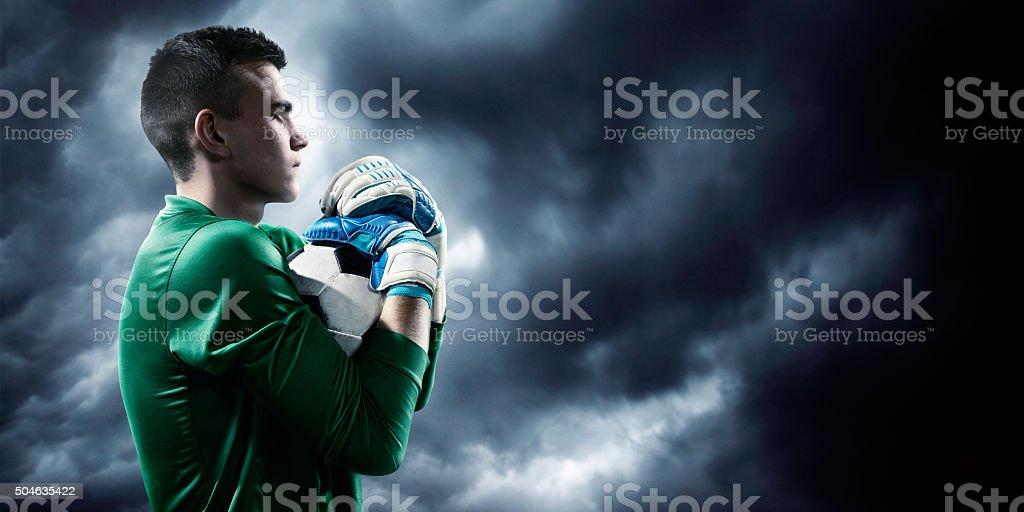 Goalkeeper catches a ball stock photo