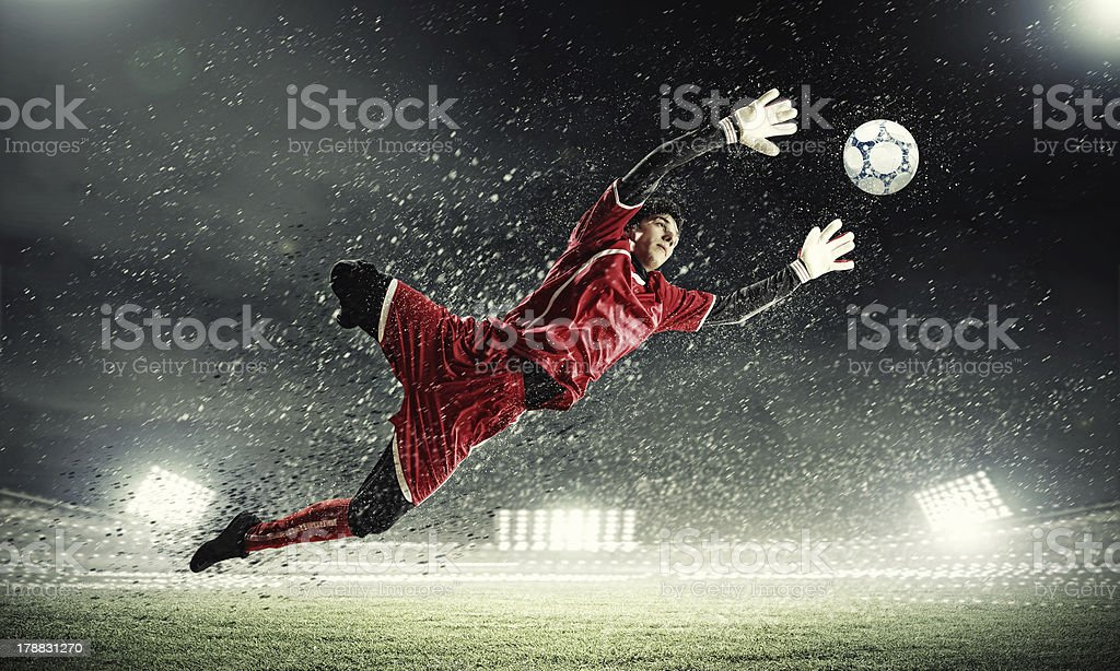 Goalkeeper catches the ball in soccer game stock photo