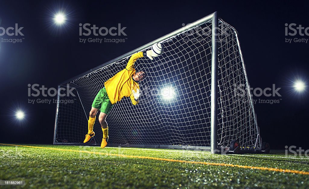 Goalkeeper jumps and tries to block a soccer ball royalty-free stock photo