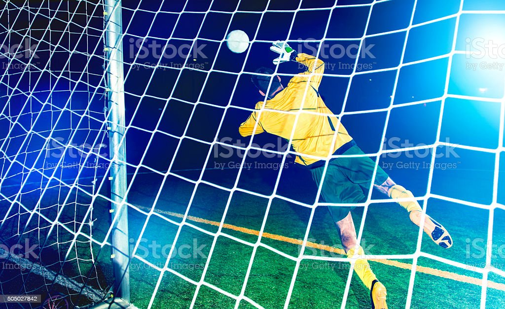 Goalkeeper jumps and tries to block a soccer ball stock photo