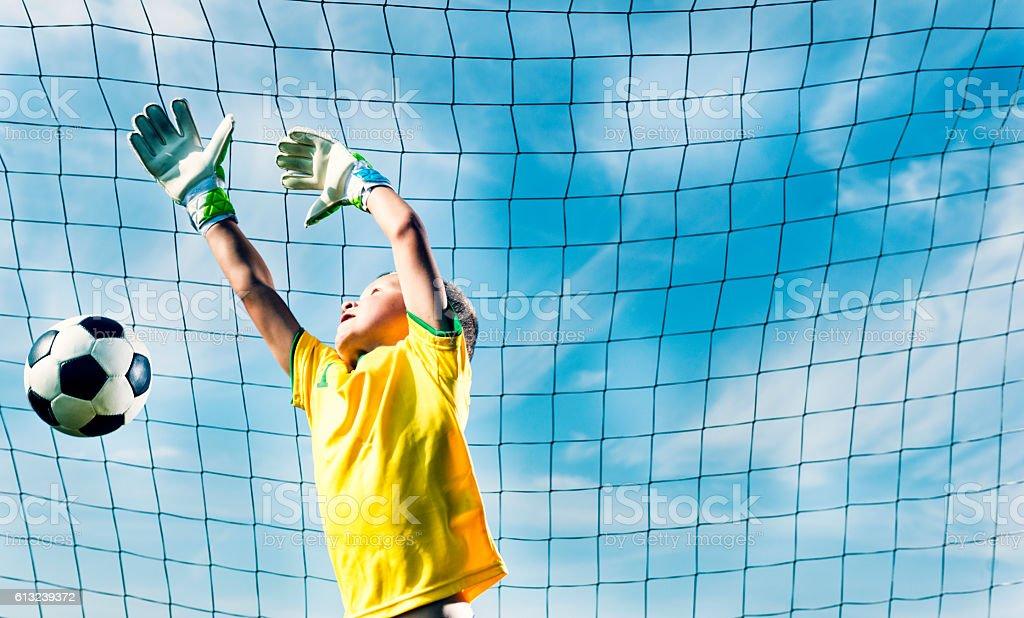 Goalkeeper jumps to block soccer ball from scoring goal stock photo