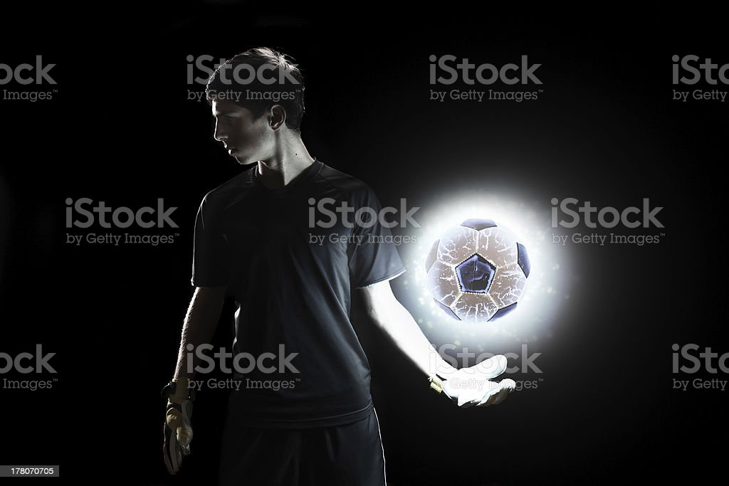 Goalkeeper standing with glowing ball stock photo