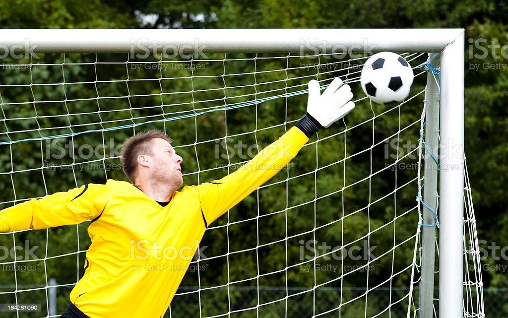 Goalkeeper tries to block perfect shot stock photo