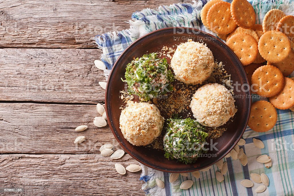 Goat Cheese balls with crackers, herbs and pumpkin seeds. Horizontal stock photo