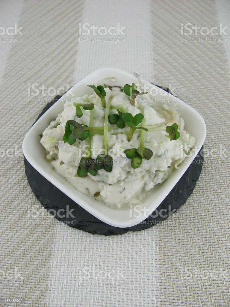 Goat cream cheese in a bowl with sprouts stock photo