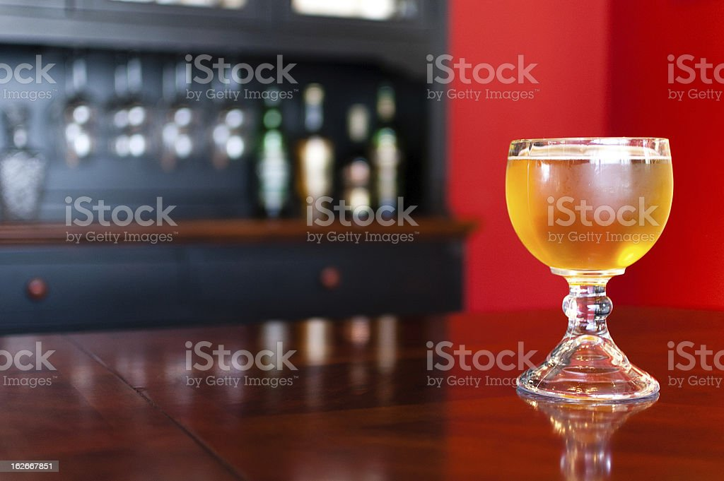 Goblet of refreshing golden beer on shiny dining table stock photo