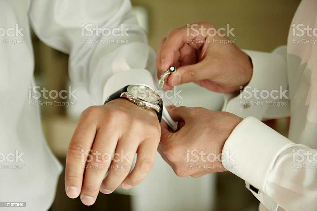 Godfather putting a cufflink in the shirt of a groom stock photo