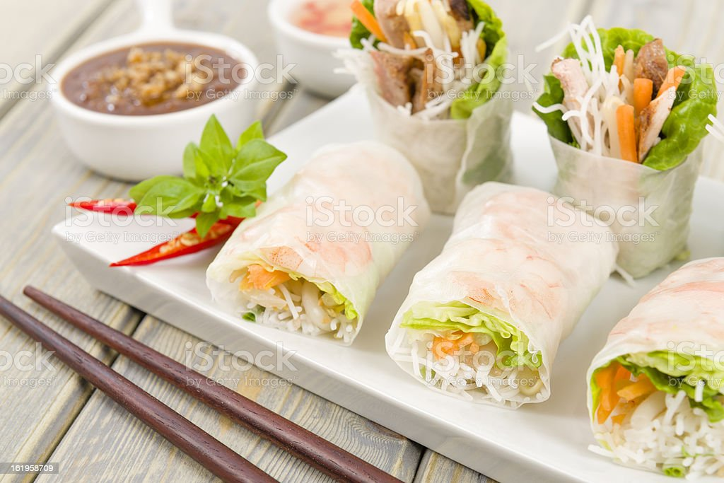 Goi cuon rolls on white plate with sauces and chopsticks stock photo