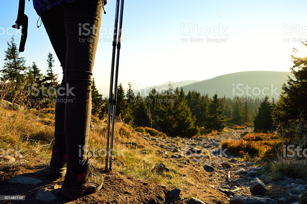 Going down a mountain trail in the sunset stock photo