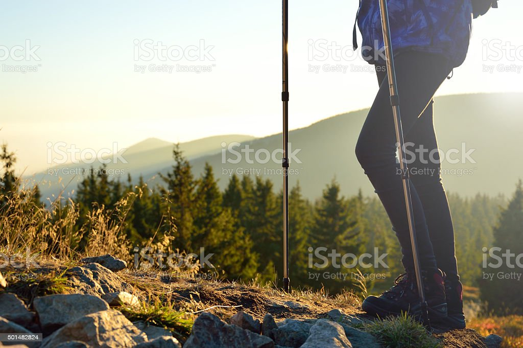 Going down a mountain trail in the sunset. stock photo
