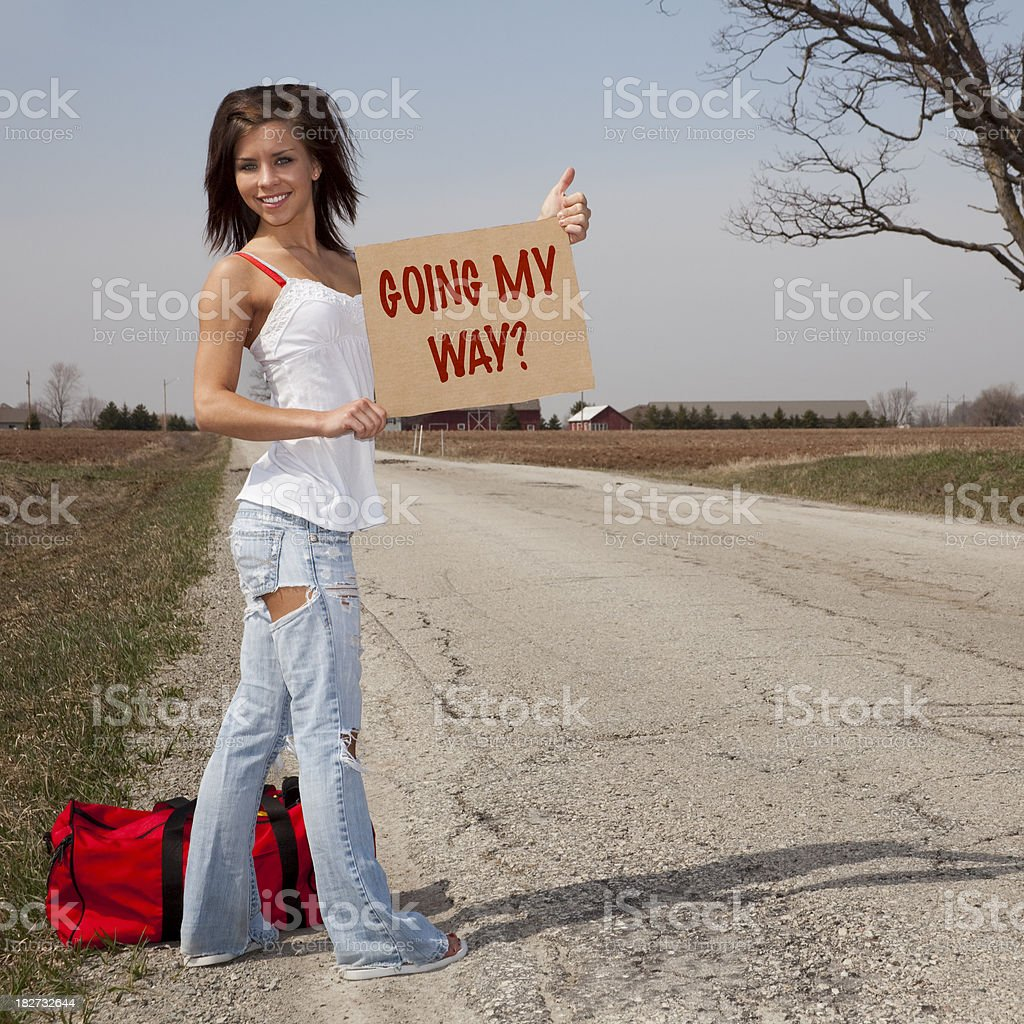 Going My Way? Beautiful Girl Hitchhiker Stranded by Roadside royalty-free stock photo