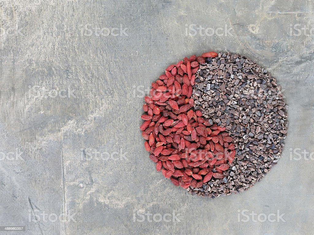 Goji berries and cacao nibs shaped in Yin Yang symbol stock photo