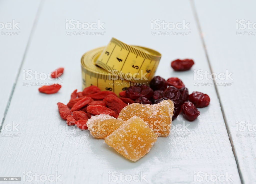 Goji berries, cranberry, candied ginger and tape measure stock photo