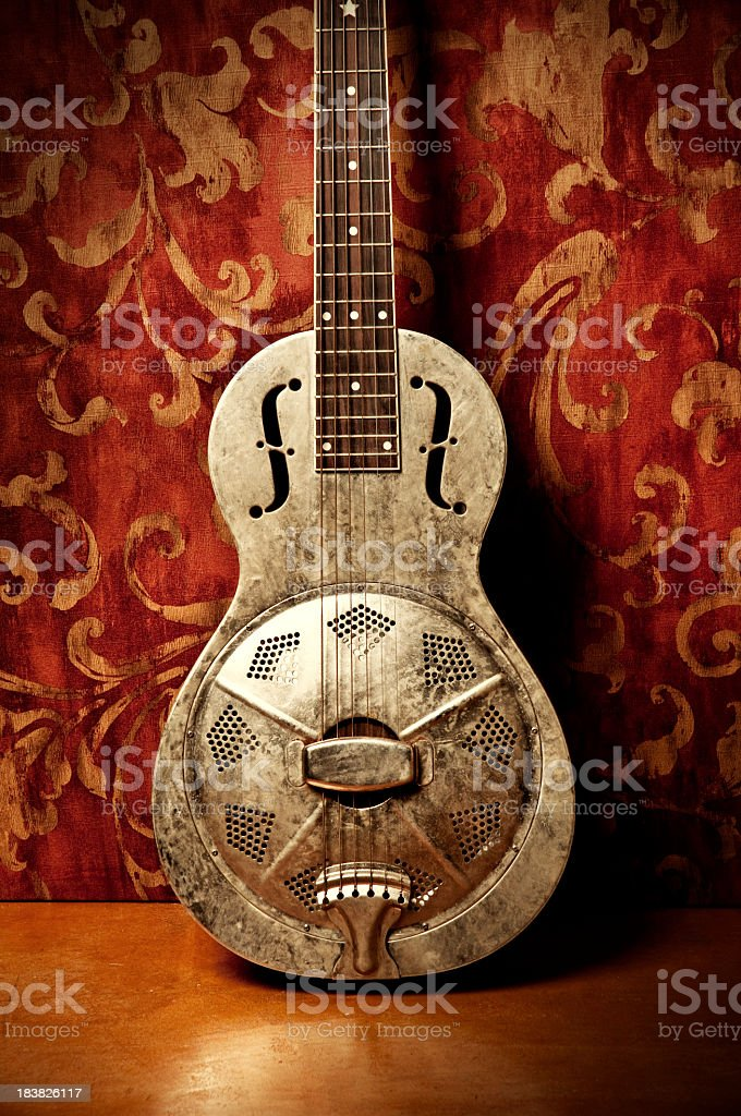 Gold acoustic guitar with red floral wallpaper stock photo