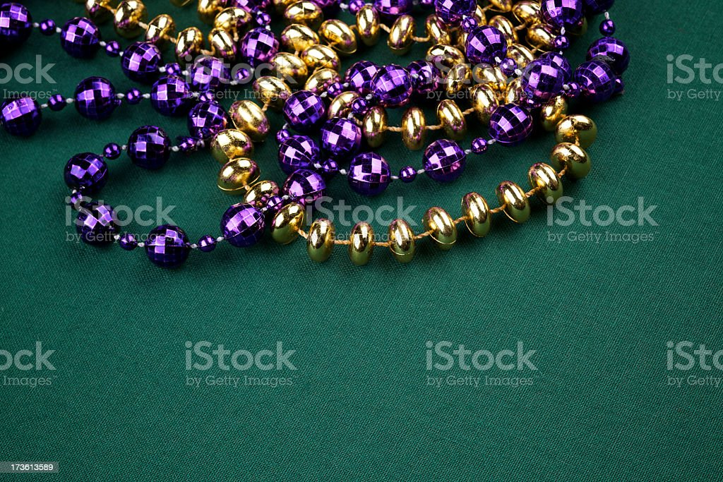 Gold and purple Mardi Gras plastic beads on green canvas royalty-free stock photo