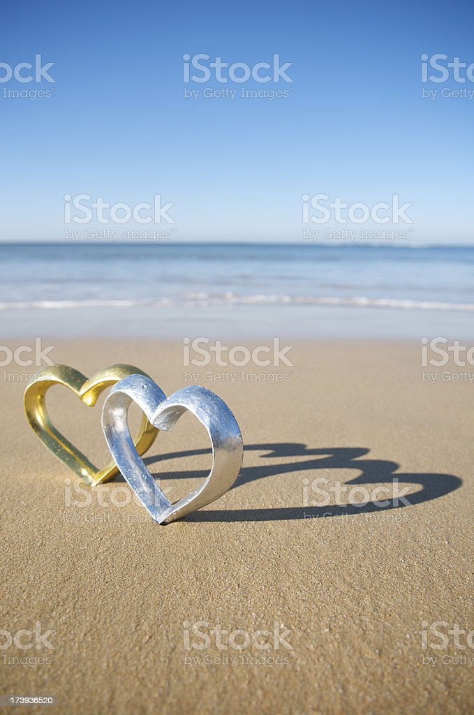 Gold and Silver Hearts Stand Together on Beach royalty-free stock photo