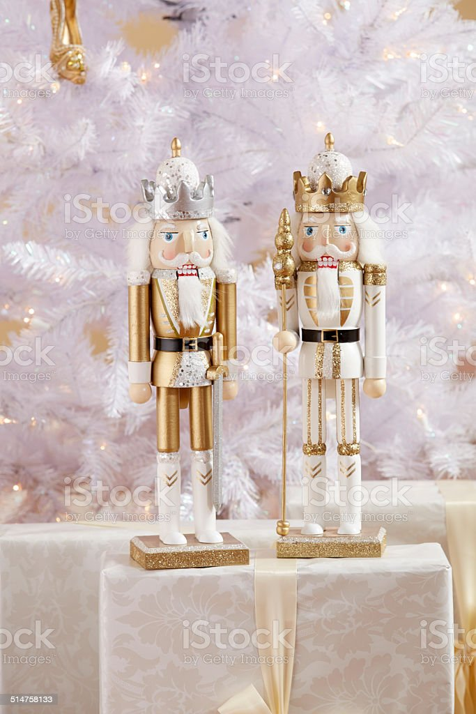 Gold and White Nutcracker in front of a white Christmass tree stock photo