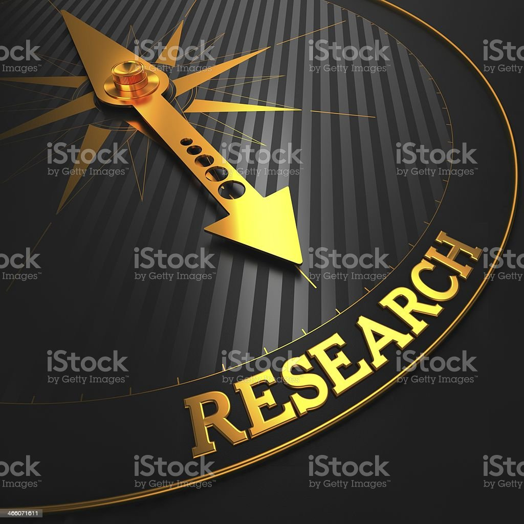 A gold arrow on a compass pointing to the word RESEARCH stock photo