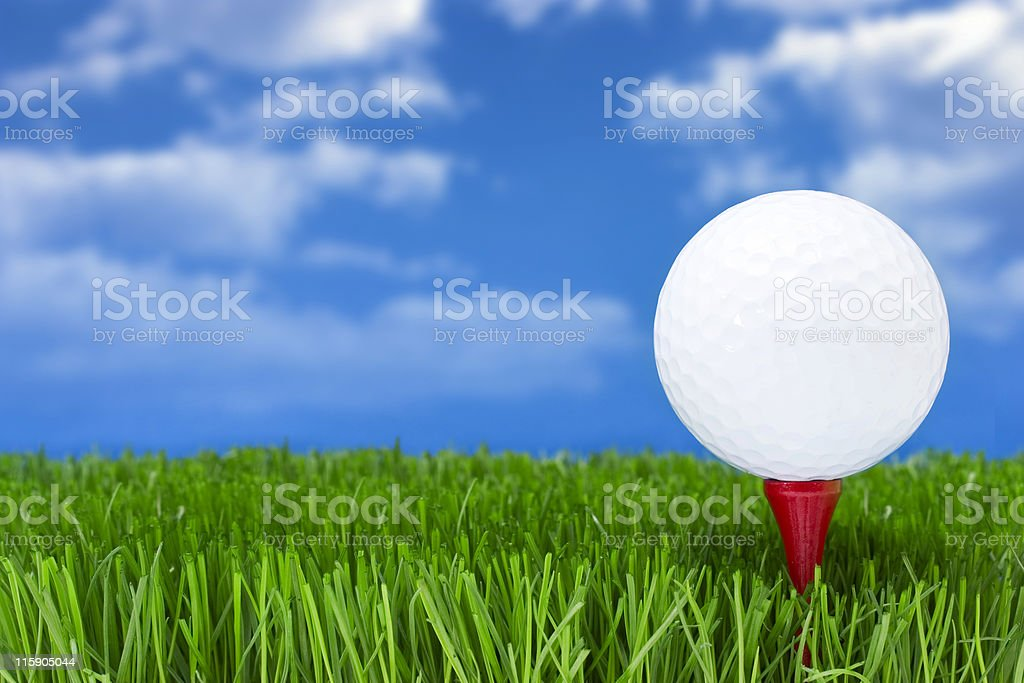 Gold ball on tee, very green grass with blue sky royalty-free stock photo