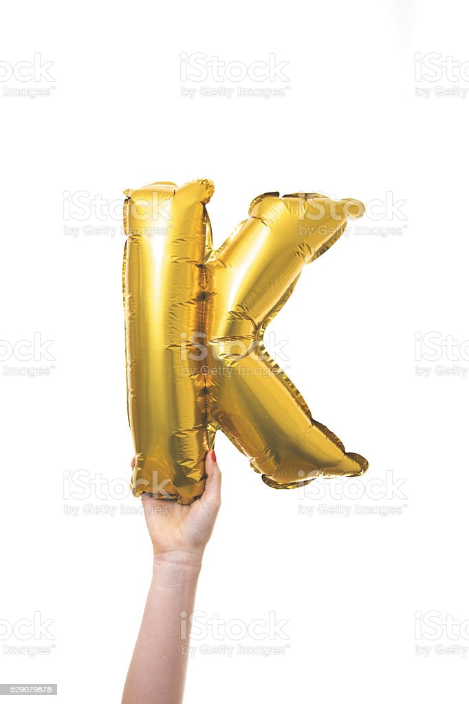 Gold balloon inflatable letter K stock photo