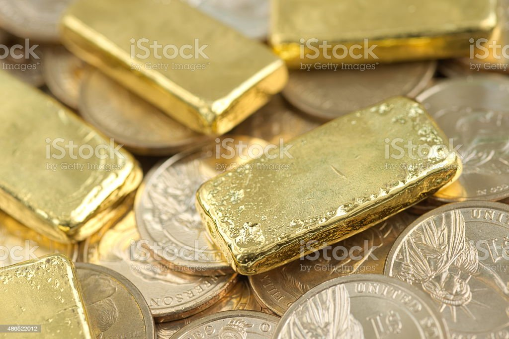 Gold bar over dollar coins stock photo