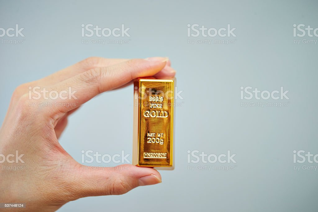 Gold bar with hand stock photo