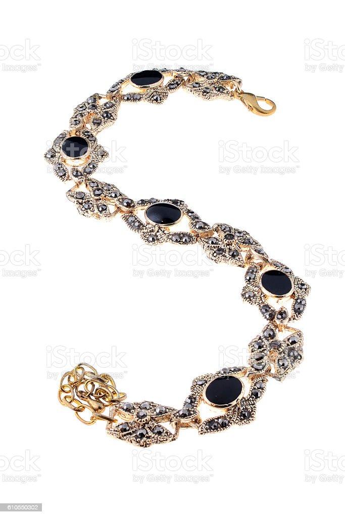 gold bracelet with black stone on a white background stock photo