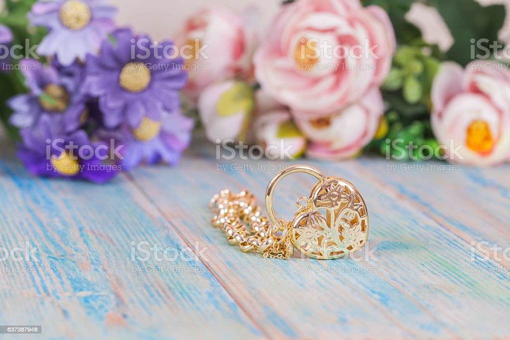 gold bracelet with heart on color wood stock photo