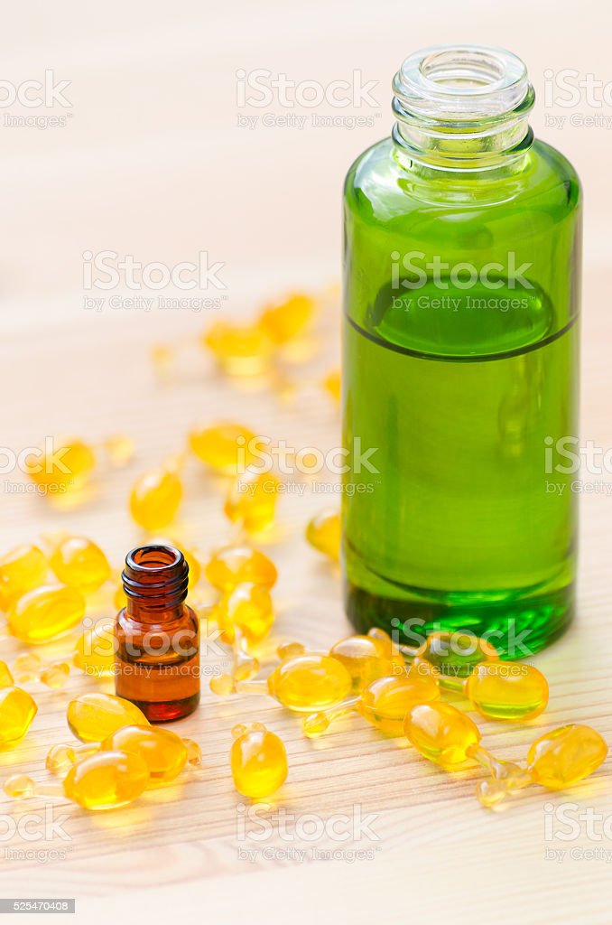 gold capsules of natural cosmetik for face and bottles with stock photo