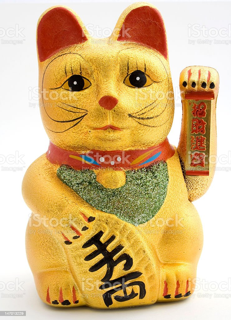 Gold ceramic statue of cat holding left arm up stock photo