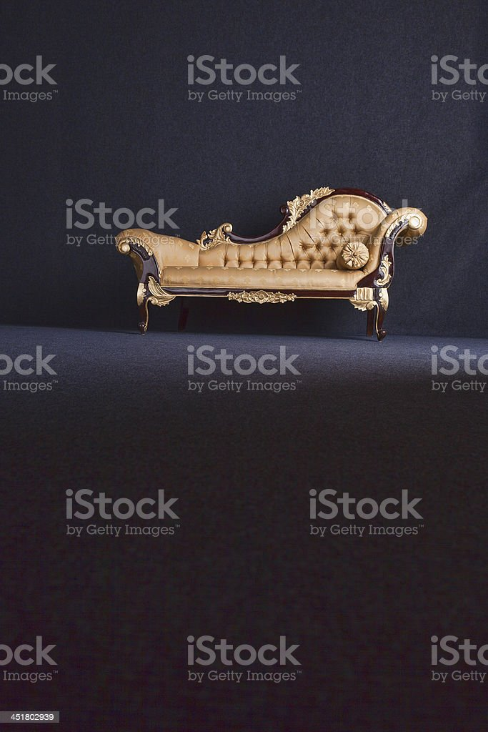 Gold Chaise Longue In A Dark Room royalty-free stock photo