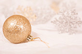 Gold Christmas ornament on white background.