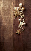 Gold Christmas ornaments on a wooden background