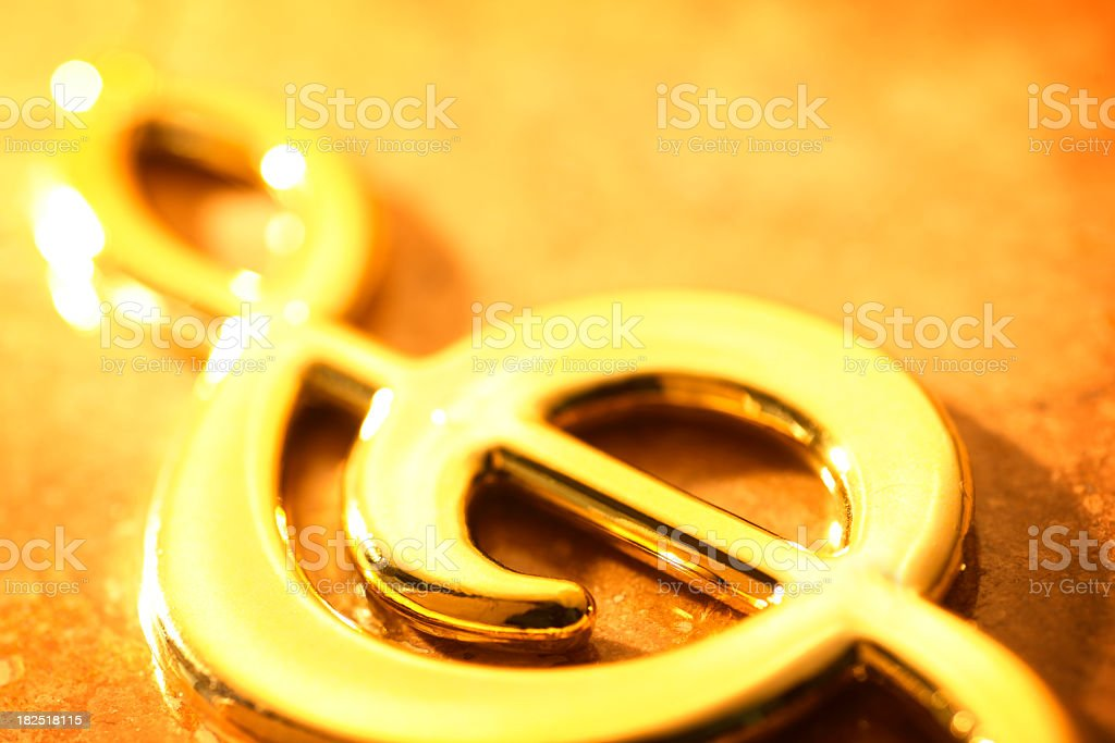 Gold chrome treble clef sitting on marble surface stock photo