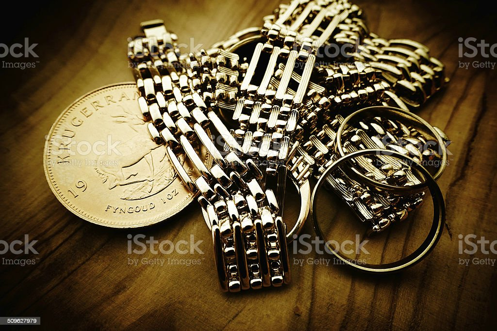 Gold coin and jewelry on wood stock photo