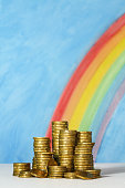 Gold coins against blue sky and rainbow background