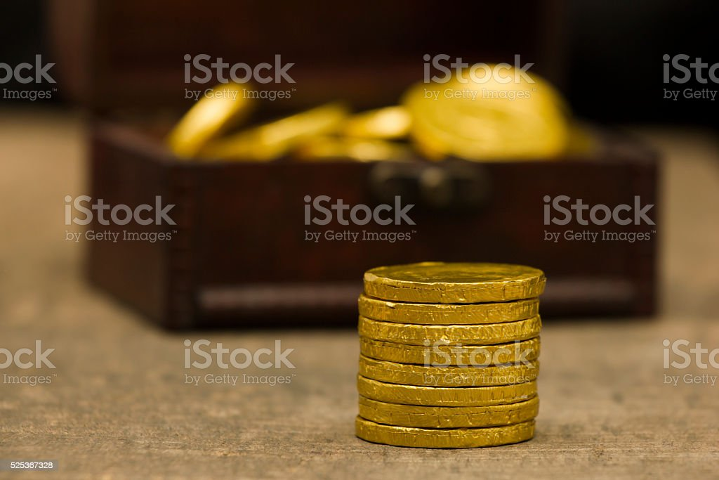 Gold coins and treasure chest on old wooden table stock photo