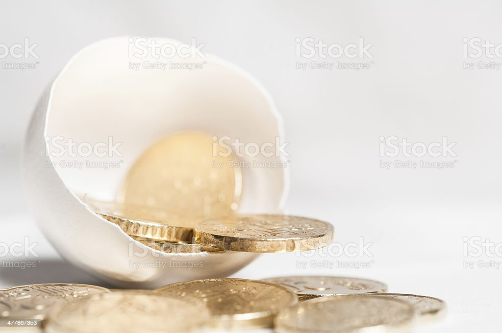 Gold coins coming out of an egg shell royalty-free stock photo
