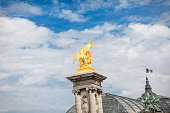 gold colored sculpture on the top of stone pillar