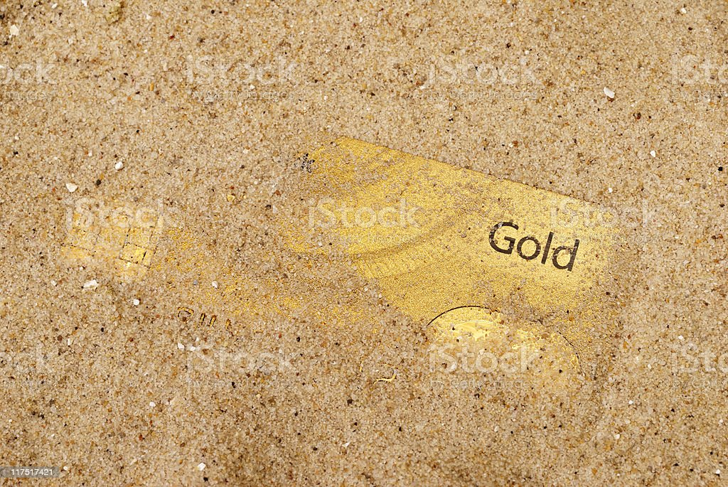 Gold credit card partially covered in sand royalty-free stock photo