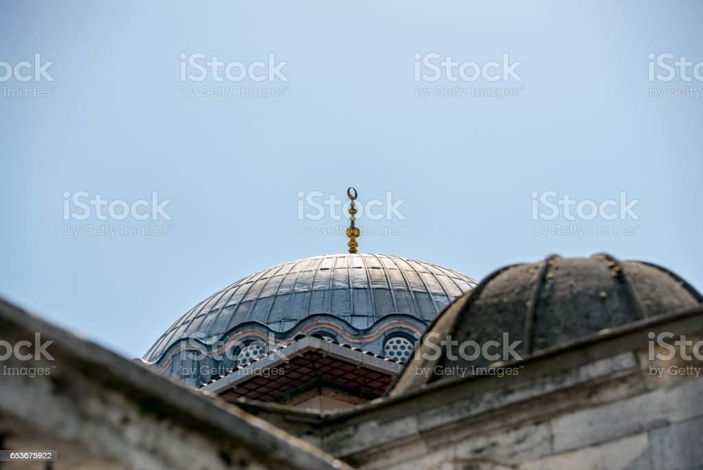 A gold crescent-topped finial (hip-knob / alem) on a mosque dome in Istanbul near Grand Bazaar with blue sky in the background. stock photo